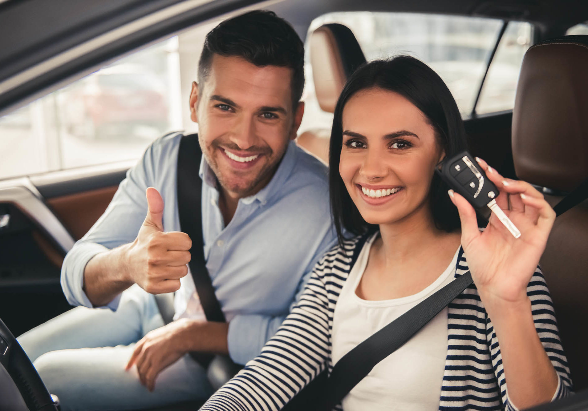 Visiting car dealership. Beautiful couple is holding a car key, looking at camera and smiling while sitting in their new car